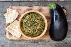 Eggplant baba ganoush and pita bread on wood Stock Photo