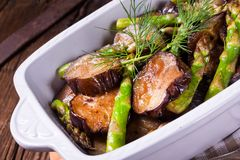 Eggplant casserole with green asparagus. A Eggplant casserole with green asparagus Stock Photos