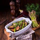 Eggplant casserole with green asparagus. A Eggplant casserole with green asparagus Royalty Free Stock Photo