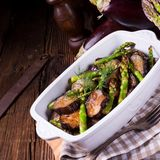 Eggplant casserole with green asparagus. A Eggplant casserole with green asparagus Royalty Free Stock Image