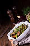 Eggplant casserole with green asparagus. A Eggplant casserole with green asparagus Royalty Free Stock Photography