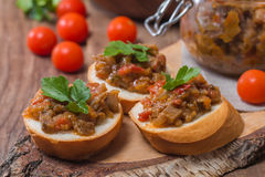 Eggplant caviar in a glass jar with croutons Stock Photos