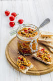Eggplant caviar in a glass jar. On a wooden board Stock Image