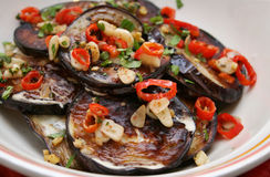 Eggplant dish. Grilled aubergine(eggplant) dish with garlic and red hot chili peppers served in a white plate Stock Image
