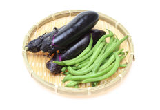 Eggplant and green beans on a bamboo colander Royalty Free Stock Images