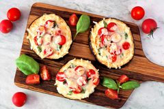Eggplant mini pizzas on a serving board against marble Stock Photography