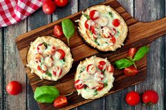 Eggplant mini pizzas on serving board against rustic wood Royalty Free Stock Photography