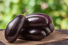 Eggplant with a napkin of burlap on wooden table  blurred green background Royalty Free Stock Photography