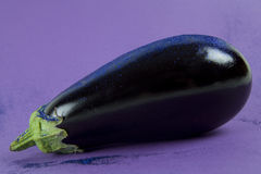Eggplant purple paillettes. Pop minimal still life photography. Shiny eggplant with blue paillettes on a purple background using gradient colors and tones on Stock Images