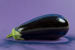 Eggplant purple paillettes. Pop minimal still life photography. Shiny eggplant with blue paillettes on a purple background using gradient colors and tones on Royalty Free Stock Photo