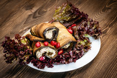 Eggplant rolls appetizer. Baba Ghanoush: eggplant rolls with lettuce and pomegranate Royalty Free Stock Photos