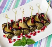 Eggplant rolls with nuts. Delicious starter of fried aubergines with nuts, herbs and pomegranate seeds Royalty Free Stock Photo