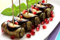 Eggplant rolls with nuts. Delicious starter of fried aubergines with nuts, herbs and pomegranate seeds Royalty Free Stock Images