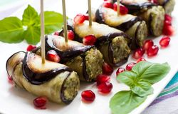 Eggplant rolls with nuts. Delicious starter of fried aubergines with nuts, herbs and pomegranate seeds Royalty Free Stock Image