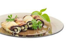 Eggplant rolls with tuna and processed cheese filling closeup. Fragment of a dark glass dish with several eggplant rolls stuffed with tuna and processed cheese stock photography