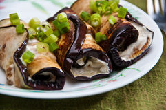 Eggplant rools with goat cheese and young onion. Eggplant rolls filled with goat cheese and decorated with young onion accompanied by a fork Stock Photos