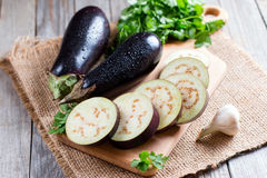 Eggplant slices on cutting board on wooden background Stock Photo