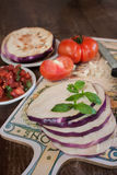 Eggplant with tomatoe and basil, recipe. Sliced eggplant and chopped tomatoes with fresh basil on cutting board Stock Photo