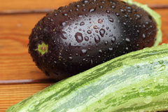 Eggplant and zucchini. With rain drops on a wet table Royalty Free Stock Images