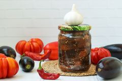 Eggplants in acute sauce of pepper, tomatoes and garlic in jar on the table. Harvest for the winter. Some vegetables are on the table royalty free stock photography