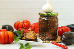 Eggplants in acute sauce of pepper, tomatoes and garlic in jar on the table. Harvest for the winter. Some vegetables are on the table stock images
