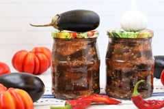Eggplants in acute sauce of pepper, tomatoes and garlic in jars on the table. Harvest for the winter. Some vegetables are on the table royalty free stock photo