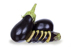 Eggplants. Fresh eggplants whole and sliced on white stock photos