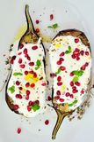 Eggplants with garlic yogurt sauceand pomegranate seeds. Grilled eggplants with garlic yogurt sauce, pomegranate seeds and mint leaves Royalty Free Stock Image