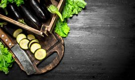 Eggplants in an old box with chopped slices. On the black chalkboard Stock Photo