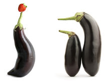 Eggplants show. Three playful eggplants and a strawberry fruit stock image