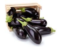 Eggplants (Solanum melongena) in wooden crate. Fresh ripe eggplants spilled out from wooden crate. Solanum melongena royalty free stock photo