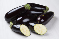 Eggplants. Some eggplants over a white wooden surface Royalty Free Stock Photo