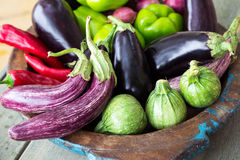 Eggplants, sweet peppers and round zucchini. On wooden plate Stock Images