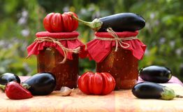 Eggplants in tomatoes in jars are located on a table in the garden. Harvesting for the winter. Fresh tomatoes, aubergines, garlic and bell peppers are on the stock photos