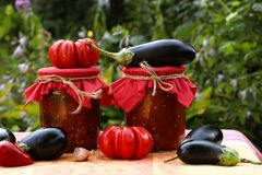 Eggplants in tomatoes in jars are located on a table in the garden. Harvesting for the winter. Fresh tomatoes, aubergines, garlic and bell peppers are on the royalty free stock photography