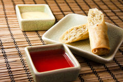 Eggroll. Yellow and red sauce on a bamboo mat Stock Image