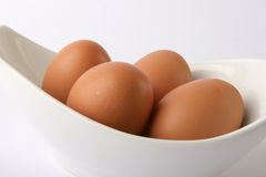 Eggs. Brown eggs in a white dish on white background. Modern and clean Stock Image