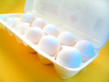 Eggs. A carton of eggs. Yellow surface and blue highlights Royalty Free Stock Photos