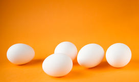Eggs. Five fresh and white easter ggs on orange background Royalty Free Stock Image