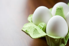 Eggs. White fresh eggs in green carton package Stock Image
