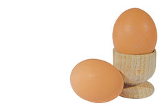 Eggs. Two tasty brown eggs and a wooden egg cup royalty free stock photos