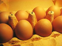 Eggs. A carton box of eggs. Yellow surface and grey highlights royalty free stock image