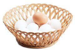 Eggs. Some white and one brown eggs in a basket over white background Stock Photo