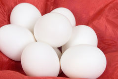 Eggs. Hard boiled eggs laying on a red silk textured cloth Stock Images