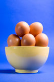 Eggs. Piled up in a yellow bowl in blue background Royalty Free Stock Photography