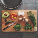 Eggs Avocado Mushroom Basil and Onion Springs on Wooden Chopping Board Stock Image