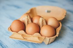 Eggs background. Closeup view of chicken eggs in carton box on wooden background.