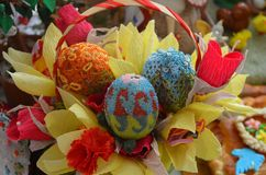 Three Easter eggs are decorated with beads. Eggs on the background of yellow and red paper flowers royalty free stock photos