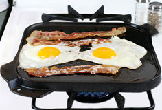 Eggs and Bacon Frying on Griddle. Two sunny side up eggs with bacon frying on a cast iron griddle, stove top with burner flame Stock Image