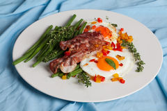 Eggs with bacon, peppers, green beans and thyme Stock Photo